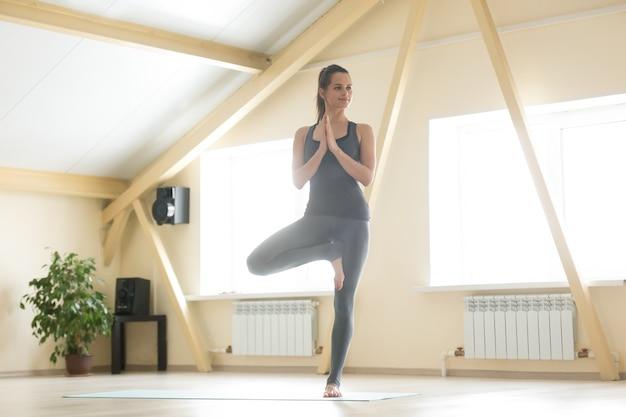 Jeune femme séduisante debout dans la pose de vrksasana, intérieur de la maison