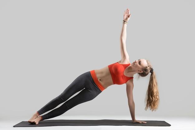 Jeune femme séduisante debout dans side plank pose, studio gris