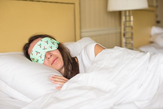 Jeune femme séduisante dort dans le lit