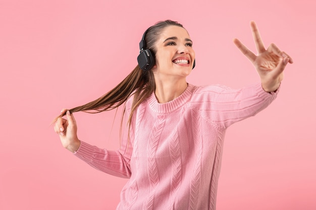 Jeune femme séduisante, écouter de la musique dans des écouteurs sans fil portant chandail rose souriant