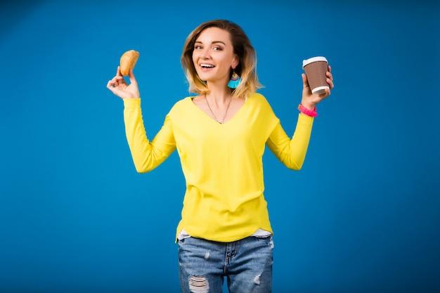 Jeune femme séduisante élégante en chemisier jaune sur bleu