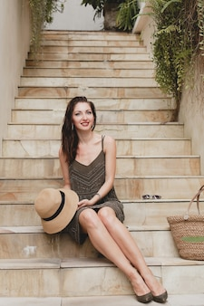 Jeune femme séduisante élégante en robe élégante assis sur les escaliers, chapeau de paille et sac, style estival, tendance de la mode, vacances, souriant, accessoires élégants, lunettes de soleil, posant sur villa tropicale à bali