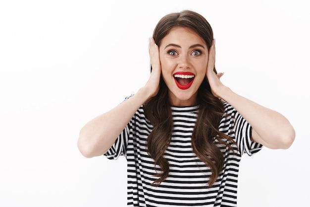 Une jeune femme séduisante et émotive, surprise, entend d'incroyables nouvelles, souriante étonnée, tient la main sur le visage et les oreilles excitées, sourit joyeusement, émerveille une surprise impressionnante
