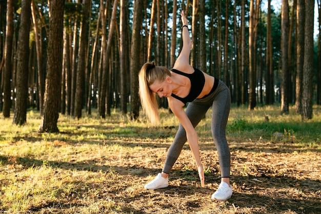 Jeune femme séduisante, faire des exercices de sport au cours de la séance d'entraînement dans le parc