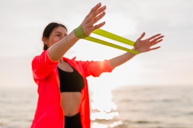 Jeune femme séduisante, faire des exercices de sport au lever du soleil du matin sur la plage de la mer, mode de vie sain, écouter de la musique sur les écouteurs, porter une veste coupe-vent rose, faire des étirements en élastique