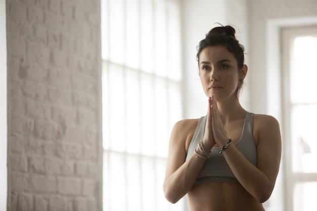 Jeune femme séduisante faisant namaste geste, studio loft blanc