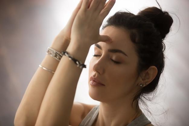 Jeune femme séduisante faisant namaste avec les yeux fermés