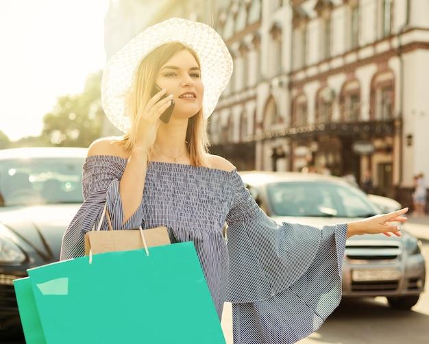 Jeune femme séduisante fait des gestes pour attraper une voiture et parler au téléphone sur la chaussée de la ville. concept d'auto-stop