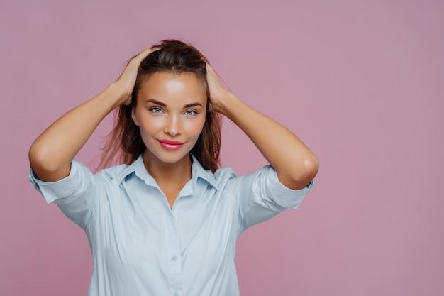 Jeune femme séduisante garde les deux mains sur les cheveux