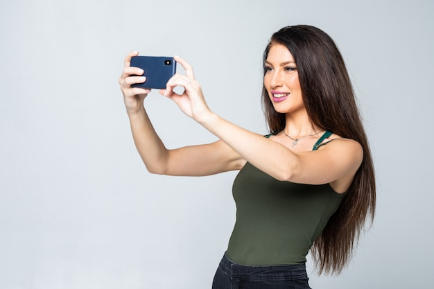 Jeune femme séduisante heureuse en robe prend des photos à l'aide de son téléphone portable, tirer