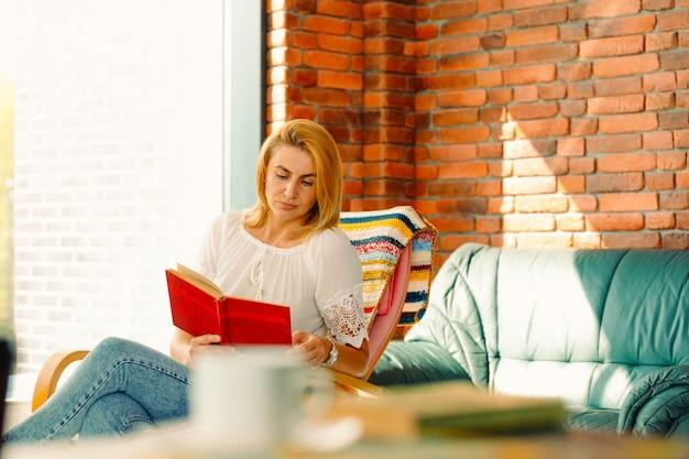 Jeune femme séduisante lit un livre, assis dans un fauteuil à bascule confortable. un bon passe-temps améliore votre humeur.