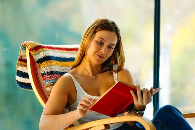 Jeune femme séduisante lit un livre, se balançant dans une chaise berçante confortable. un bon passe-temps améliore votre humeur.