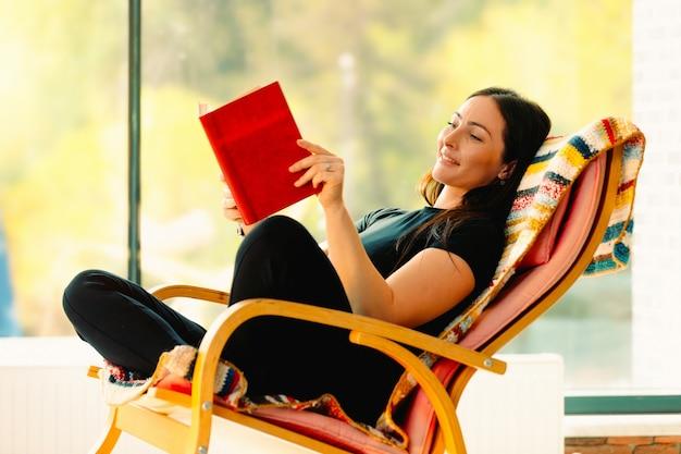 Jeune femme séduisante lit un livre se balançant dans une chaise berçante confortable. .