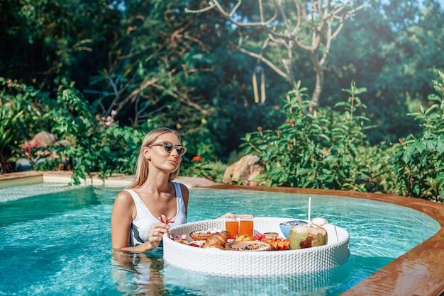 Jeune femme séduisante mangeant de la nourriture asiatique nage dans une piscine avec table flottante dans un hôtel moderne et luxueux.