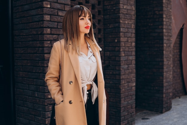 Jeune femme séduisante en manteau beige posant dans la rue
