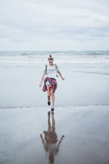 Jeune femme séduisante marchant le long du rivage de l'océan sur une plage de sable fin