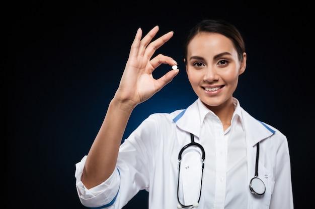 Jeune femme séduisante médecin montrant la pilule et souriant