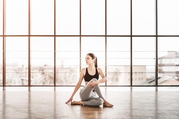 Jeune femme séduisante mince avec des cheveux longs, pratiquer l'yoga à l'intérieur.