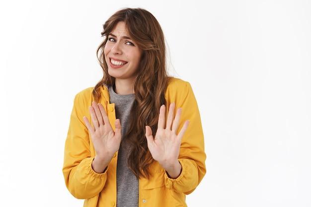 Jeune femme séduisante nerveuse maladroite s'excusant pour son refus d'essayer d'échapper à une situation inconfortable reculer se baissant souriant tenir la main rejet arrêter le geste