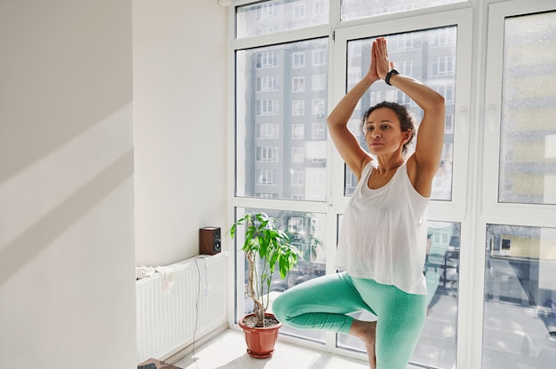 Jeune femme séduisante à la peau foncée concentrée debout sur la position de l'arbre pendant la pratique du yoga