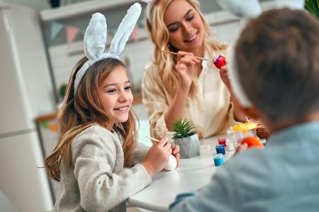 Une jeune femme séduisante avec une petite fille et un garçon mignons se préparent pour la célébration de pâques. une famille heureuse portant des oreilles de lapin passe du temps ensemble avant pâques tout en peignant des œufs.