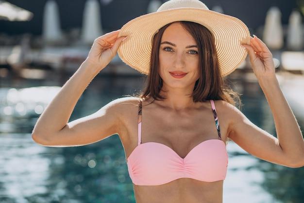 Jeune femme séduisante portant un chapeau et debout au bord de la piscine