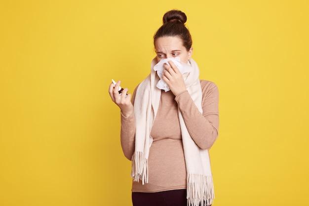 Jeune femme séduisante portant un pull beige et une écharpe blanche, une femme enceinte ayant le nez qui coule, tenant un spray nasal dans les mains, décide de l'utiliser ou non, posant isolée sur un mur jaune.