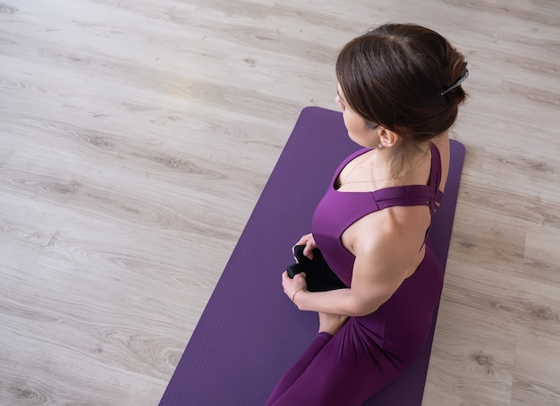 Jeune femme séduisante pratiquant le yoga. femme assise dans padmasana lotus pose. pratique d'exercices de yoga.