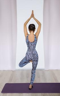 Jeune femme séduisante pratiquant le yoga. femme debout sur une jambe. pratique d'exercices de yoga.