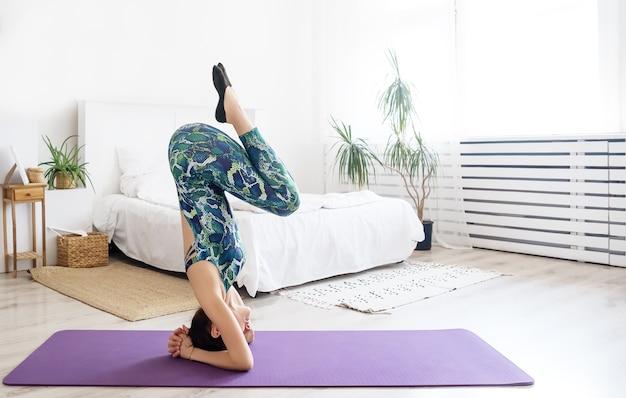 Jeune femme séduisante pratiquant le yoga. femme faisant l'exercice du poirier. pratique d'exercices de yoga.