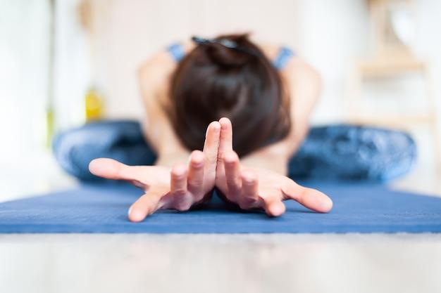Jeune femme séduisante pratiquant le yoga. femme qui s'étend des muscles du dos. pratique d'exercices de yoga.