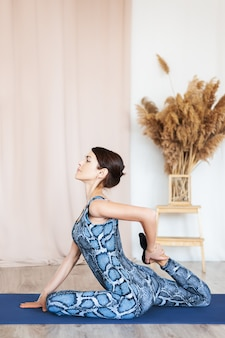 Jeune femme séduisante pratiquant le yoga. femme qui s'étire les jambes. pratique d'exercices de yoga.