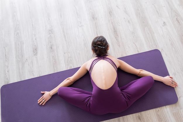 Jeune femme séduisante pratiquant le yoga. femme s'étirant le dos. pratique d'exercices de yoga.
