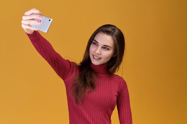 Jeune femme séduisante, prendre des photos sur la mémoire sur fond isolé.