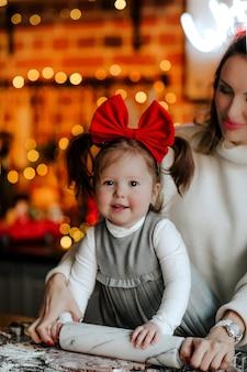 Jeune femme séduisante en pull d'hiver blanc et petite fille bébé enfant en robe et arc rouge faisant des cookies dans la cuisine.