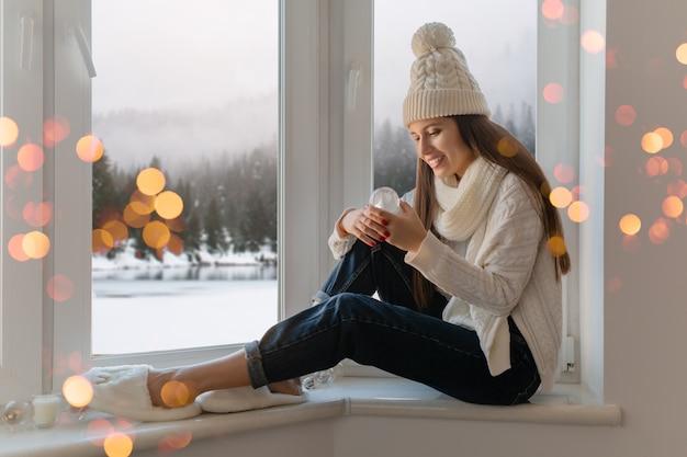 Jeune femme séduisante en pull tricoté blanc élégant, écharpe et chapeau assis à la maison sur le rebord de la fenêtre à noël tenant boule de neige en verre décoration actuelle, vue sur la forêt d'hiver, lumières bokeh