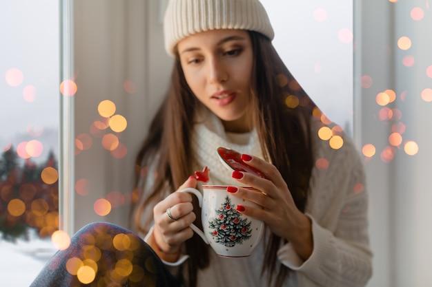 Jeune femme séduisante en pull tricoté blanc élégant, écharpe et chapeau assis à la maison sur le rebord de la fenêtre à noël tenant la tasse de boire du thé chaud, vue de fond de forêt d'hiver, lumières bokeh