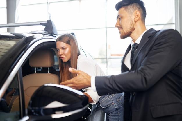 Jeune femme séduisante à la recherche d'une nouvelle voiture dans une salle d'exposition de voiture