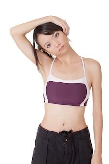 Jeune femme séduisante de remise en forme faisant des excises extensibles sur un mur blanc.