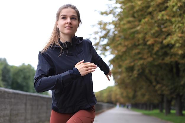 Jeune femme séduisante de remise en forme sportive qui court tout en faisant de l'exercice à l'extérieur au coucher du soleil ou au lever du soleil.