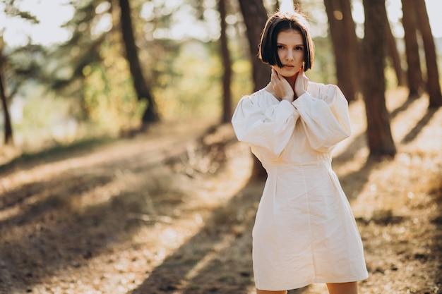 Jeune femme séduisante en robe blanche en forêt