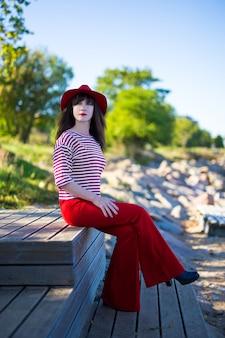 Jeune femme séduisante en rouge assis dans le parc
