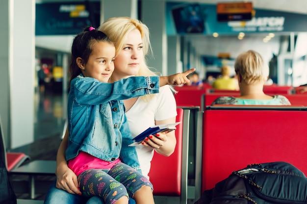 Jeune femme séduisante et sa petite fille mignonne sont prêtes à voyager