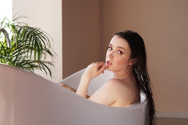 Jeune femme séduisante se détendre dans le bain - plante dans la salle de bain - journée ensoleillée