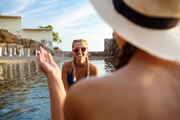 Jeune femme séduisante se réjouissant, nageant dans la mer