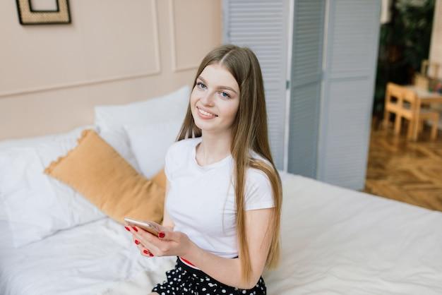 Jeune femme séduisante se reposant sur un canapé blanc à la fenêtre à la maison