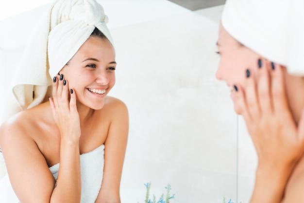 Jeune femme séduisante avec une serviette blanche sur la tête et le corps avec reflet dans le miroir dans la salle de bain
