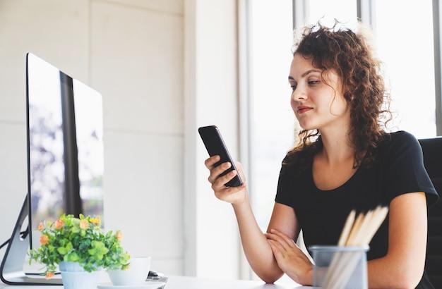 Jeune femme séduisante souriante à l'aide de la messagerie smartphone pour les entreprises au bureau