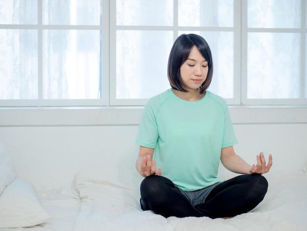 Jeune femme séduisante souriante de yogi pratiquant le yoga
