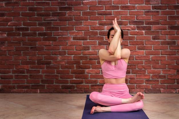 Jeune femme séduisante sportive en vêtements roses, pratiquer le yoga